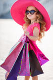 Fashionable little girl in a hat with shopping bags Stock Image