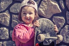 A fashionable little girl is holding a skateboard and playing outside, the beautiful emotions of a child. stock photos