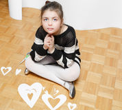 Fashionable little girl sitting and dreaming on hardwood floor with paper hearts cut for valentines day Royalty Free Stock Image