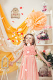 Fashionable little girl throwing petals in studio Royalty Free Stock Image
