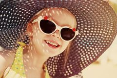 Fashionable little girl wearing a hat and sunglasses stock image