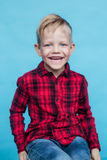 Fashionable little kid with red shirt. Fashion. Style. Studio portrait over blue background Stock Images