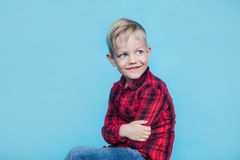 Fashionable little kid with red shirt. Fashion. Style. Studio portrait over blue background royalty free stock image