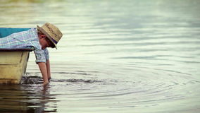 Fashionable little pal sitting in the boat and dangles his hands in the water stock footage