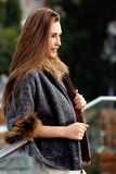 Fashionable long-haired girl dressed in dress and short sheepskin coat with fur poses in the street stock photography