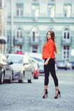 Fashionable look, hot day model of a young woman walking in the city, wearing a red jacket and black pants, blond hair outdoors ov. Er the city warm background Royalty Free Stock Photos