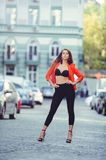 Fashionable look, hot day model of a young woman walking in the city, wearing a red jacket and black pants, blond hair outdoors ov. Er the city warm background Royalty Free Stock Photo