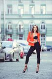 Fashionable look, hot day model of a young woman walking in the city, wearing a red jacket and black pants, blond hair outdoors ov. Er the city warm background Stock Photography