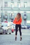 Fashionable look, hot day model of a young woman walking in the city, wearing a red jacket and black pants, blond hair outdoors ov. Er the city warm background Stock Photo
