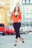 Fashionable look, hot day model of a young woman walking in the city, wearing a red jacket and black pants, blond hair outdoors ov. Er the city warm background Stock Photos