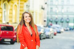 Fashionable look, hot day model of a young woman is walking in the city, wearing a red jacket, blond hair and a smile outdoors ove. R the city warm background Royalty Free Stock Images