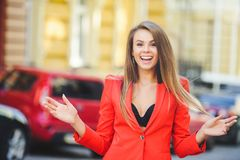 Fashionable look, hot day model of a young woman is walking in the city, wearing a red jacket, blond hair and a smile outdoors ove. R the city warm background Stock Images