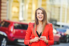 Fashionable look, hot day model of a young woman is walking in the city, wearing a red jacket, blond hair and a smile outdoors ove. R the city warm background Royalty Free Stock Image