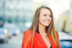 Fashionable look, hot day model of a young woman is walking in the city, wearing a red jacket, blond hair and a smile outdoors ove. R the city warm background Stock Photo