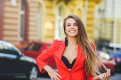 Fashionable look, hot day model of a young woman is walking in the city, wearing a red jacket, blond hair and a smile outdoors ove. R the city warm background Stock Image
