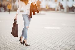 Fashionable look of incognito stylish woman walking at street.
