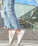 Fashionable look. White shirt, jeans, brown leather bag and sneakers shoes Royalty Free Stock Images