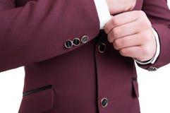 Fashionable male model fixing elegant suit jacket sleeve with bu Royalty Free Stock Photos