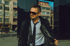 Fashionable male model looking away with sunglasses and leather Stock Photos