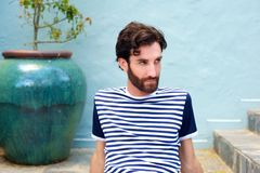 Fashionable male model in striped shirt sitting outdoors Royalty Free Stock Photos