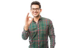 Fashionable Male Showing Ok Gesture Over Plain Background. Fashionable young male showing OK gesture while smiling over plain background stock photo