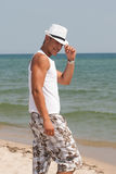 Fashionable male with white fedora hat at the beach. Enjoying summer travel holiday by the sea Royalty Free Stock Photo