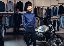 Fashionable man with full beard trendy dressed posing near retro sports motorbike at the men`s clothing store. Young fashionable man with full beard trendy royalty free stock photography