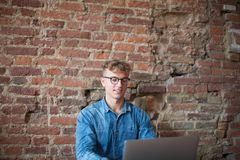 Young stylish hipster guy successful lifestyle writer using laptop computer, sitting in modern interior. Fashionable man in glasses reading message in internet Royalty Free Stock Images