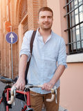 Fashionable man holding his bike Royalty Free Stock Images