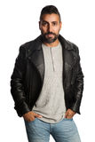 Fashionable man in leather jacket. Trendy man standing against a white background wearing a black jacket and jeans, feeling relaxed and comfortable Stock Image