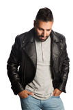 Fashionable man in leather jacket. Trendy man standing against a white background wearing a black jacket and jeans, feeling relaxed and comfortable Stock Images