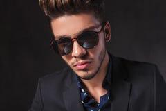 Fashionable man posing at the camera wearing sunglasses in studi Stock Image