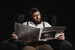 Fashionable man reading business newspaper while sitting in armchair Royalty Free Stock Photography