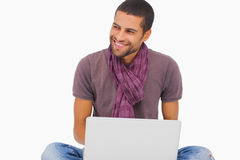 Fashionable man sitting on floor using laptop and looking away Stock Image