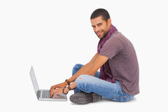 Fashionable man sitting on floor using laptop smiling at camera Stock Photography