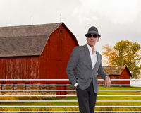 Fashionable man standing in from of a red barn Royalty Free Stock Photos