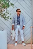 Fashionable man in sunglasses dressed in modern elegant clothes holds a fish sculpture while standing against a white. Fashionable man in sunglasses dressed in Royalty Free Stock Images