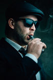 Fashionable man in sunglasses and a leather cap smokes Stock Photo