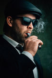 Fashionable man in sunglasses and a leather cap smokes Royalty Free Stock Photo