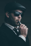 Fashionable man in sunglasses and a leather cap smokes Stock Images