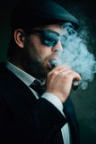 Fashionable man in sunglasses and a leather cap smokes Stock Photos