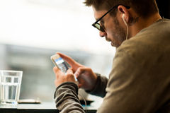 Fashionable man working on his phone in the coffee shop. Portrait of young man posing at the coffee shop with his phone and earphones Stock Photo