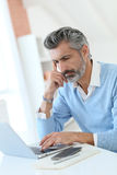 Fashionable mature man working from home with laptop Stock Photo