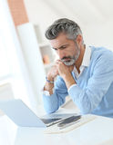 Fashionable mature man working from home with laptop Royalty Free Stock Photo