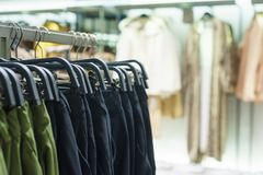 Fashionable men`s and women`s coat on hangers in a modern clothing store. Stylish clothes for man and women. Sale and shopping in stores. Modern textiles and Royalty Free Stock Image