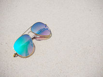 Fashionable mirror sunglasses on sand Stock Photos