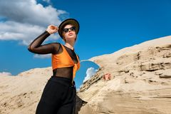 Fashionable model posing with round mirror. Near dune stock photography