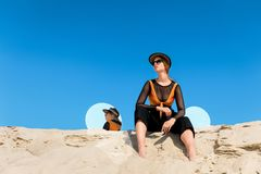 Fashionable model posing on sand with round mirrors with reflection of. Blue sky stock images