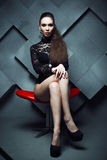 Fashionable model sitting in a red chair Royalty Free Stock Image