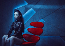 Fashionable model sitting in a red chair Stock Photo